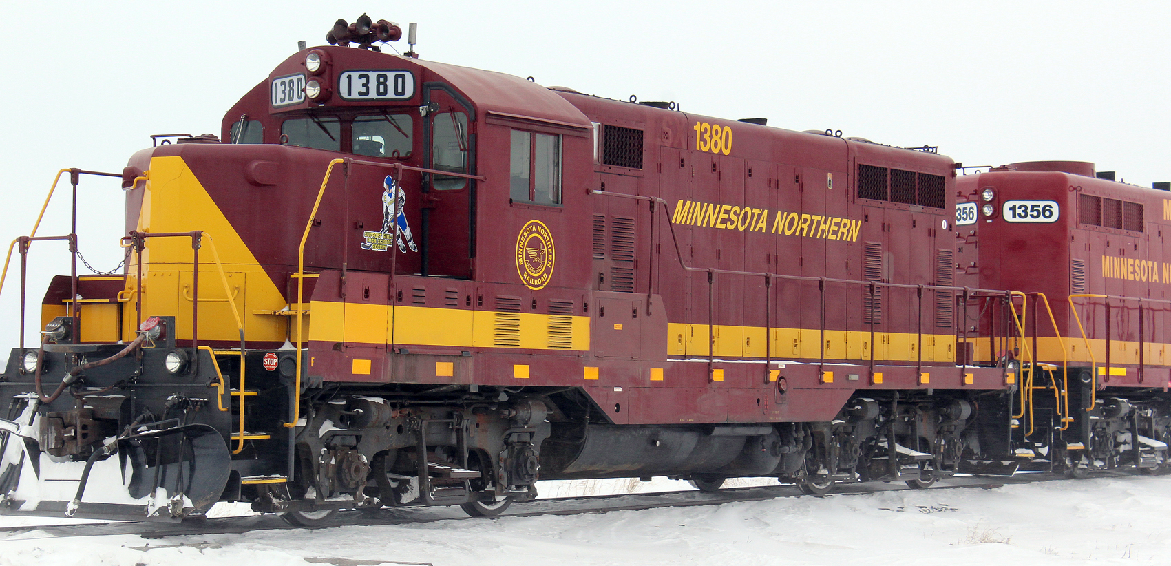 Decals on two Minnesota Northern Railroad locomotives draw attention to high school girls hockey, particularly Prowler girls hockey. On this side, the decal depicts a generic girl wearing a Prowler girls hockey jersey assigned to Lincoln High School senior Grace Bergland. Three other decals feature jerseys assigned to the other three seniors on the team.
